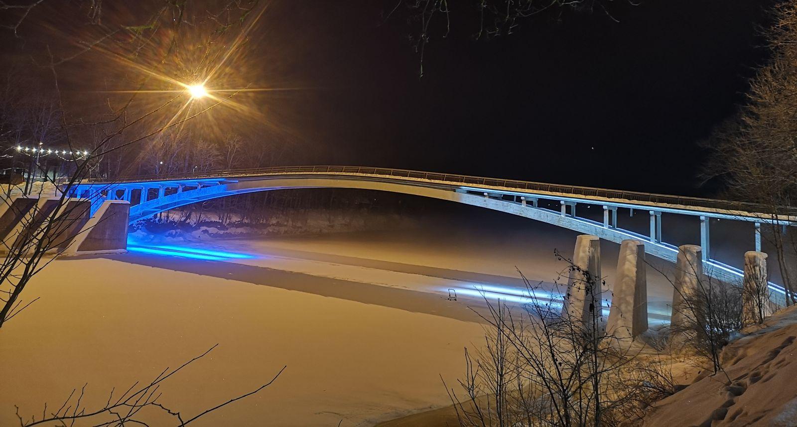 Lokveida gājēju tilts pāri Ogres upei mirdz Igaunijas karoga krāsās